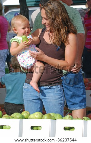 Mother with baby daughter picking out pears to buy at a farmer's market.