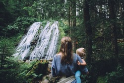 Mother with baby girl admiring waterfall in the woods