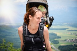 Mother with baby in backpack carrier is hiking in mountains. Tourist is carrying a child on his back in the nature of Slovenia with beautiful view of the valley.