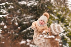 Mother with baby in her arms walking in the Park in winter in beige clothes. Mom plays with her child outside in winter. Happy family.