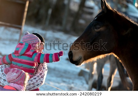 mother with baby love Horse gallops in winter
