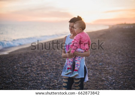 mother with baby on beach in...
