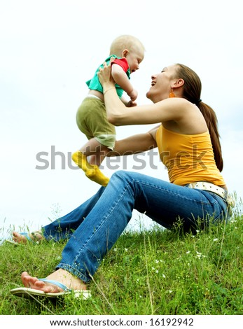 Mother with  baby  on the meadow under blue sky