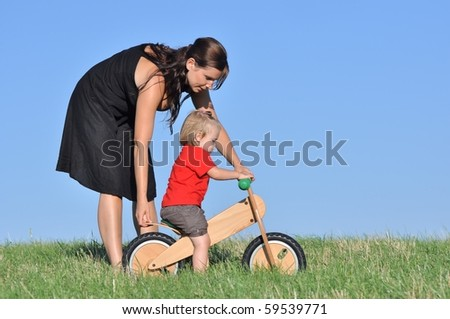 Mother with baby on the meadow with bike