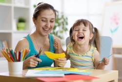 mother with child daughter in a yellow dress fun cut scissors colored paper