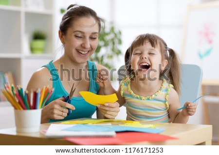mother with child daughter in a yellow dress fun cut scissors colored paper Сток-фото ©