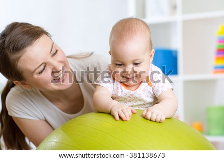 Mother with child doing exercises with green gymnastic ball at home. Concept of caring for the baby\'s health.