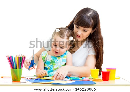 Mother with child girl draw and cut together