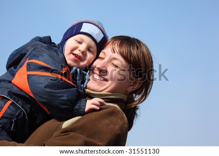 Mother with child on hands on spring sky background