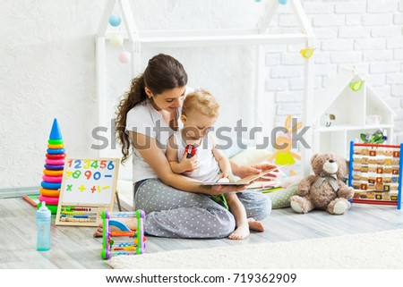 Mother with child playing educational toys and reading book in the room