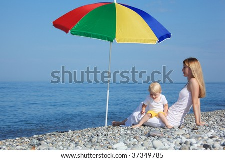 Mother with child under  colored umbrella on pebble beach