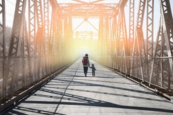 Mother with child walks away on the bridge into the light