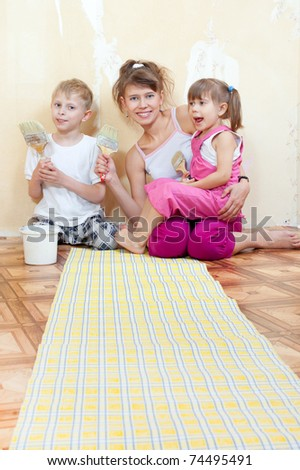 Mother with children doing repairs together, wallpaper on the floor