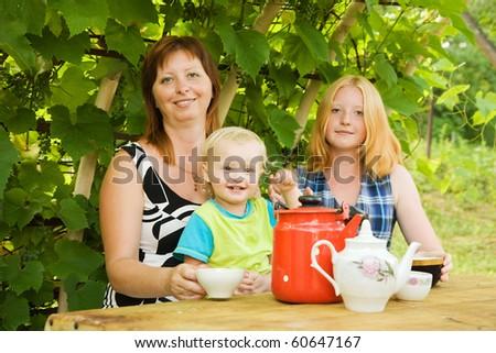 mother with children having tea at pergola