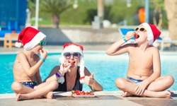 Mother with children in Santa hats celebrate the New Year in hot countries. The family eats strawberries and swims in the pool. New Year, Christmas.