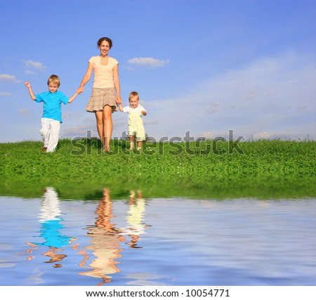 mother with children on meadow and water