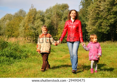 Mother with children on walk in wood, front view