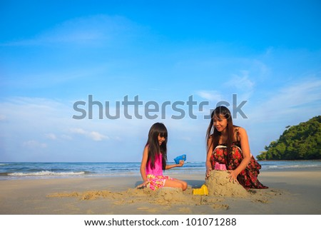 Mother with children playing with sand on beach with blue sky