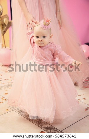 Mother with cute baby girl in room decorated for birthday party