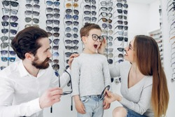 Mother with cute son. Family buy glasses. Father in a white shirt