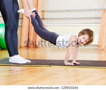 Mother with daughter exercising in sport hall