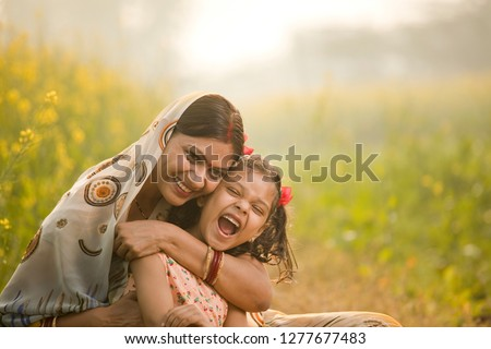 Mother with daughter having fun at agriculture field