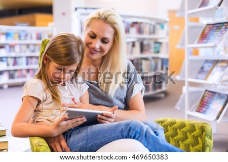 Mother with daughter look at their touch pad tablet device together in library. Happy family, preschool concept. Parent educating children. #469650383