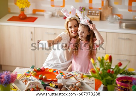 Mother with daughter making selfie while painting Easter eggs