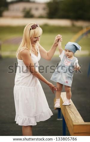 mother with daughter on horizontal bar balance