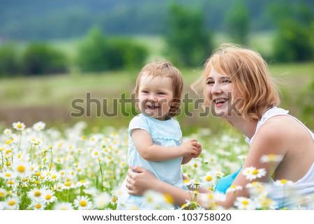 Mother with daughter on the camomile meadow