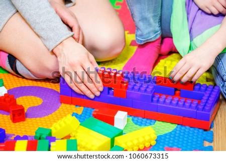 Mother with daughter playing with toy bricks #1060673315