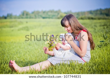 Mother with daughter sitting in a field