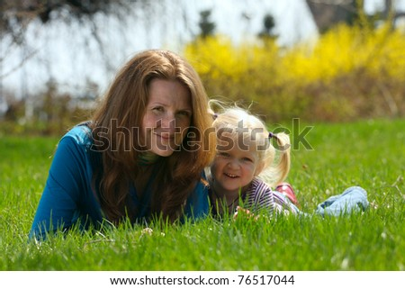 mother with  daughter sitting on a grass at the park