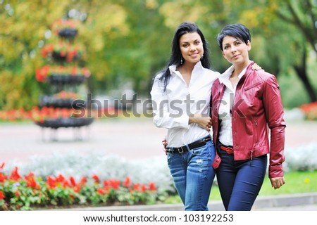 Mother with daughter walking in autumn park
