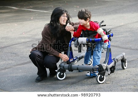 Mother with disabled son walking outdoors with walker, medical mobility equipment Stock photo ©