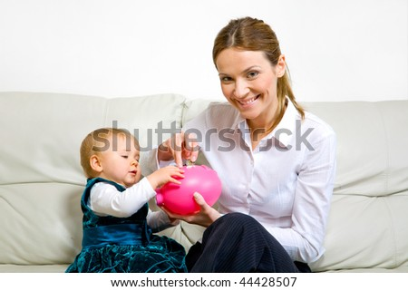 mother with her adorable baby and a piggy bank