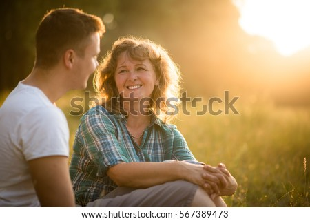 Mother with her adult son against nature background. Family bond concept.