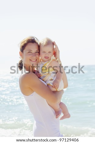 mother with her baby on beach in crimea