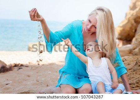 Mother with her baby playing on the beach