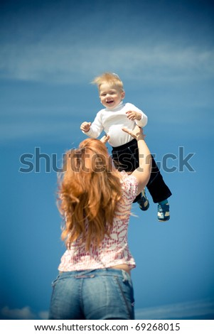 Mother with her baby playing outdoor against the sky