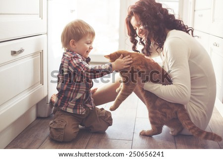 Mother with her baby playing with pet on the floor at the kitchen at home - Shutterstock ID 250656241