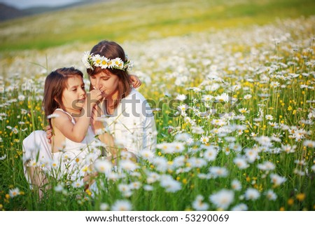 Mother with her child playing in camomile field