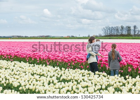 Mother with her child walks between of the purple tulips field