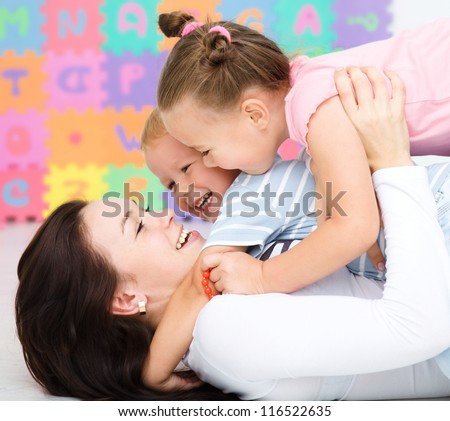 Mother with her children are having fun rolling on a floor - stock photo
