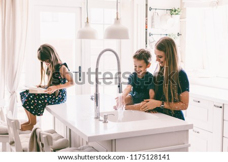 Mother with her children playing with water in kitchen sink at home. Happy lifestyle family moments.