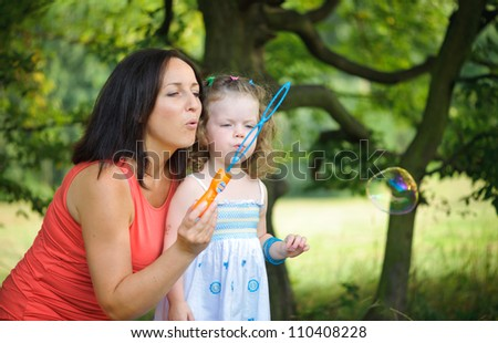 Mother with her daughter are blowing soap bubles