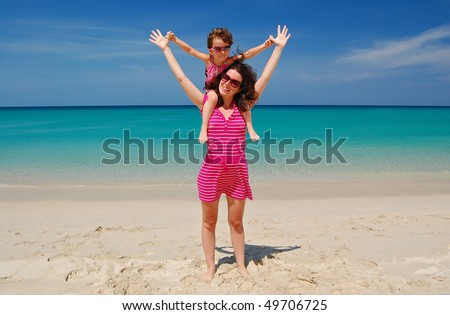Mother with her daughter having fun on beautiful tropical beach. Family vacation