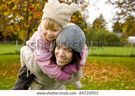 Mother with her daughter in park in autumn