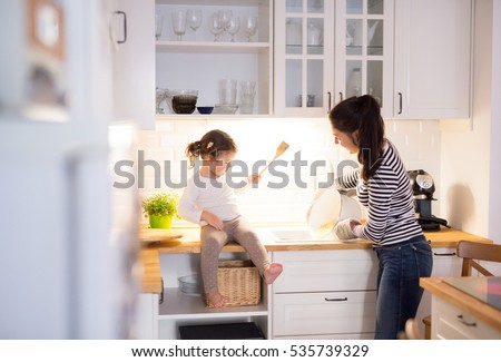 Mother with her daughter in the kitchen cooking together #535739329