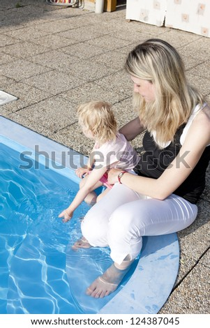 mother with her daughter sitting by swimming pool